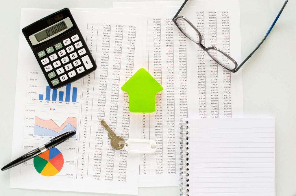 Buying or saving for a house  in a conceptual image with , calculator, eyeglasses,  pen, keys, house shape and documents. Top view. lease accounting.